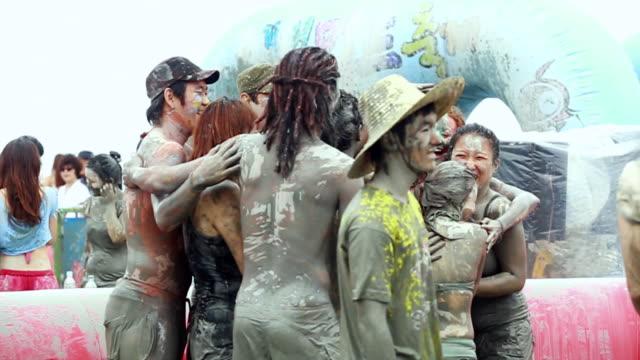 ms slo mo people enjoying boryeong mud festival / boryeong, chungcheongnam-do, south korea - mud stock videos and b-roll footage