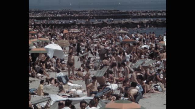 vídeos de stock, filmes e b-roll de people enjoying crowded beach, coney island, new york city, ny, usa - 1941