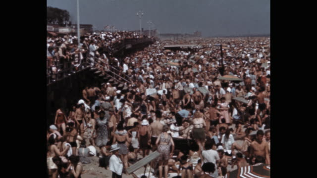 people enjoying crowded beach, coney island, new york city, ny, usa - 仰向きに寝る点の映像素材/bロール