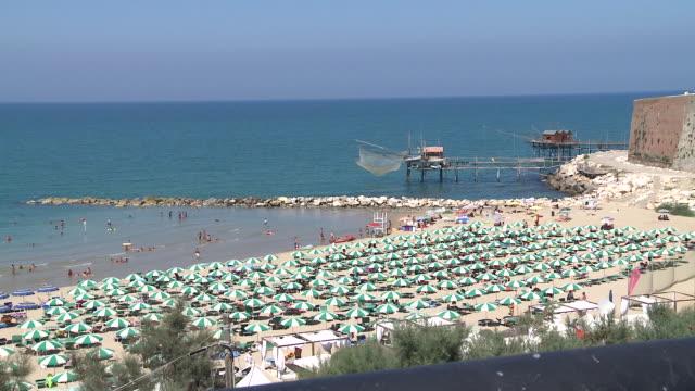 ws people enjoying in ocean and long line of umbrellas on beach / termoli, molise, italy - affollato video stock e b–roll