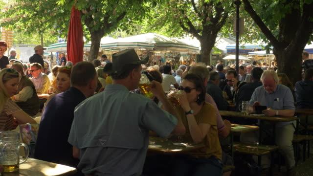 people enjoying leisure time in bavarian beer garden - ドイツ点の映像素材/bロール