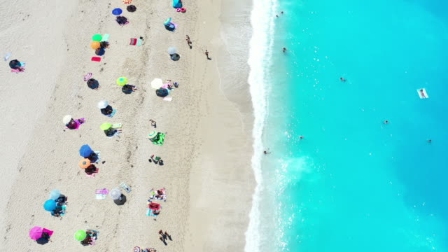 people enjoying milos beach, lefkada, greece. - parasol stock videos & royalty-free footage