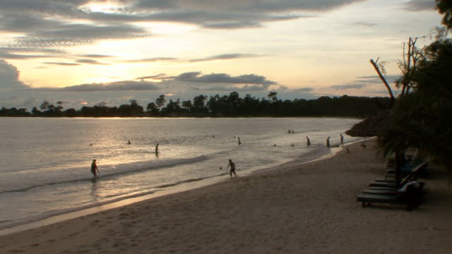 vidéos et rushes de ws people enjoying on exotic tropical beach at sunset / sihanoukville, cambodia - arbre tropical