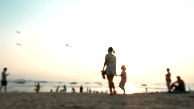 vidéos et rushes de les gens appréciant sur le coucher du soleil de plage. défocalisé - sans mise au point and équilibre