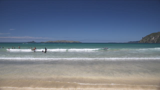vídeos y material grabado en eventos de stock de ws people enjoying surf and waves on beach/ northand, new zealand - bañador de natación