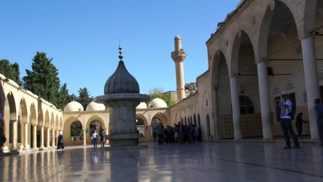 people enjoying the inner yard of the beautiful mosque of abraham in the old part of urfa - minaret bildbanksvideor och videomaterial från bakom kulisserna