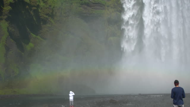 People enjoying the rainbow over the Skógafoss waterfall in Iceland