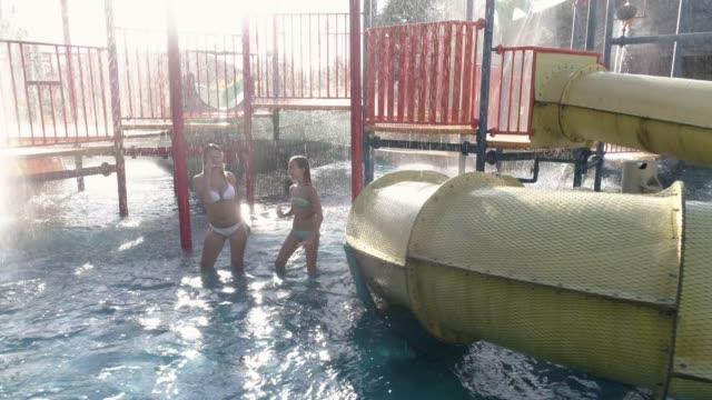 menschen genießen die wasserrutschen in einem wasserpark - wasserrutsche stock-videos und b-roll-filmmaterial