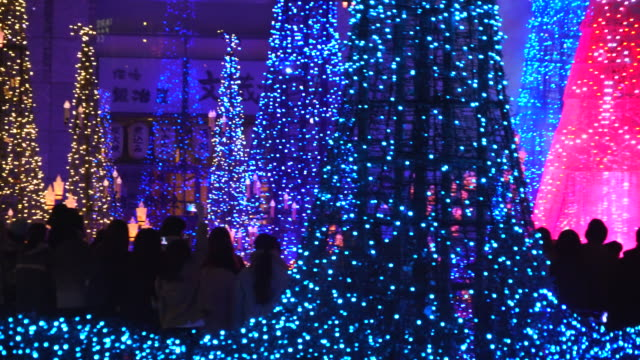 people enjoying to watching and photographing the caretta illumination show, which is illuminated by approximately 250,000 led lights every 20 minutes in caretta shopping mall shiodome tokyo japan on january 16 2018. - disney stock videos & royalty-free footage