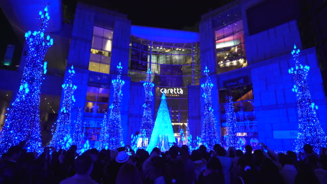people enjoying to watching and photographing the caretta illumination show, which is illuminated by approximately 250,000 led lights every 20 minutes in caretta shopping mall shiodome tokyo japan on january 16 2018. - continuity stock videos & royalty-free footage