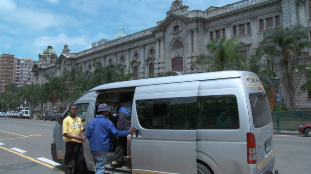 PAN People enter taxi in front of colonial building, Durban City Hall / Durban, South Africa