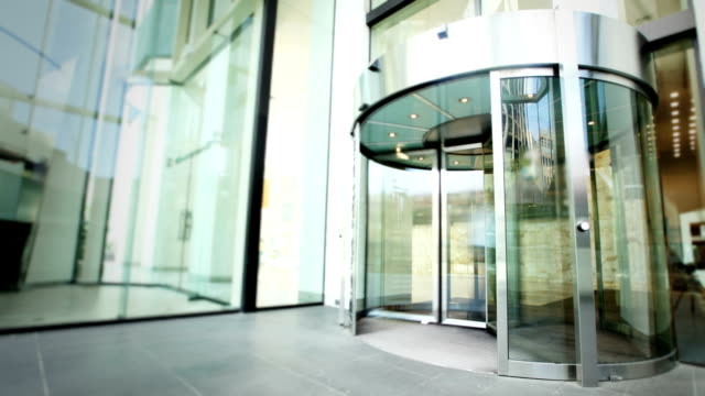 people entering and leaving office building - revolving door stock videos & royalty-free footage