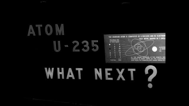 people entering atomic exhibit w/ men in uniform standing off to sides 'u-235' on wall bg atom u-235 what next' on wall w/ chart. model of atom. - 大量破壊兵器点の映像素材/bロール