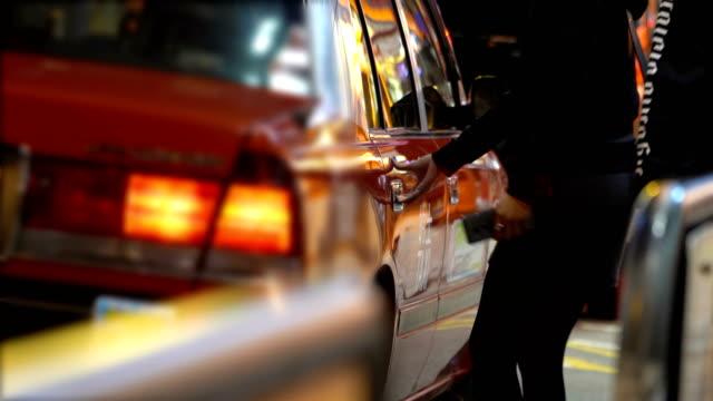 people entering in car at taxi cabs queue in mong kok, hong kong at night - mong kok stock videos & royalty-free footage