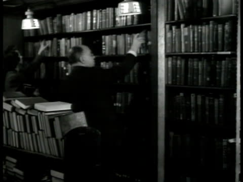 people entering library building int ms elderly man picking out book from shelf ms women checking out book at librarian's counter cu books on shelf... - librarian stock videos & royalty-free footage