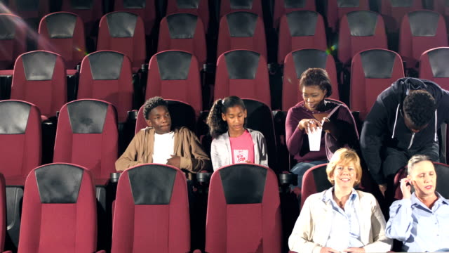 people entering movie theater, finding seats - seat stock videos & royalty-free footage