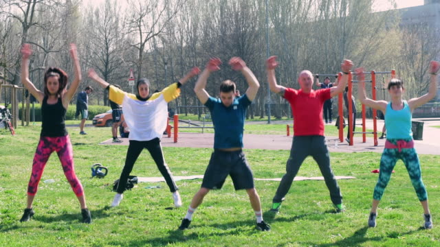 people exercising in park - star jump stock videos & royalty-free footage