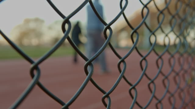 people exercising on running track fence in foreground - good posture stock videos & royalty-free footage