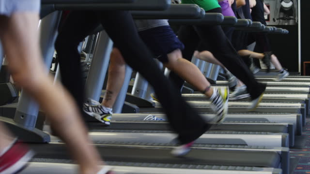 ms tu people exercising on treadmills in gym / draper, utah, usa - エクササイズ用具点の映像素材/bロール
