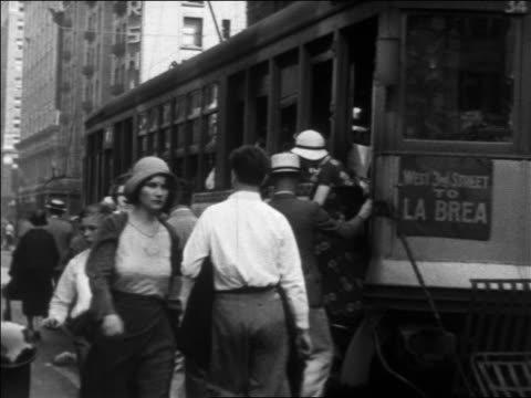b/w 1930 people exiting + boarding trolley on city street / los angeles, ca - 1930 stock-videos und b-roll-filmmaterial