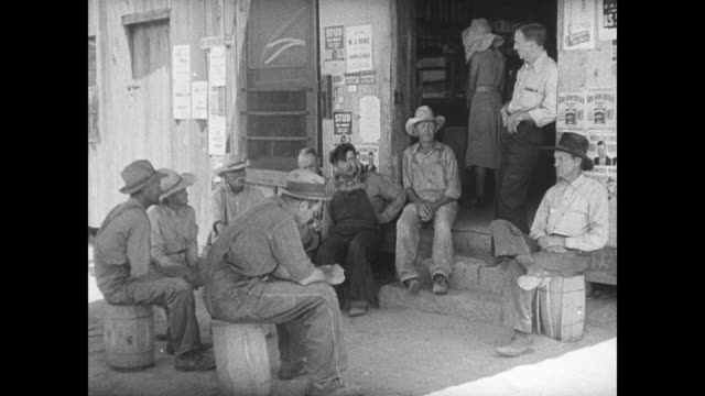 people farmers sitting around outside local store newspaper article about money paid under aaa men talking by rural post office ext department of... - new deal stock-videos und b-roll-filmmaterial