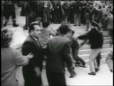 B/W 1956 people fighting hitting each other with nightsticks in riot / Rome / newsreel