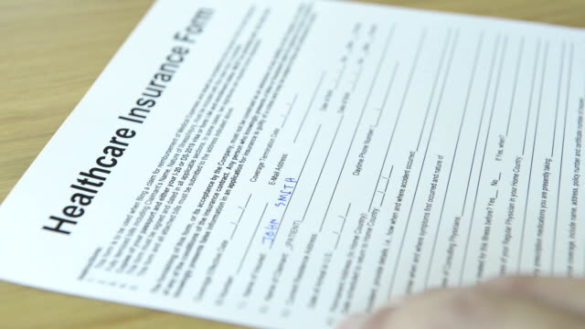 cnglmed545 - people filling out generic healthcare insurance forms. - part of stock videos & royalty-free footage