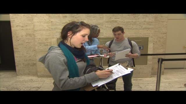 vídeos de stock, filmes e b-roll de wgn people filling out paperwork at voting registration center on october 09 2012 in chicago illinois - título de eleitor
