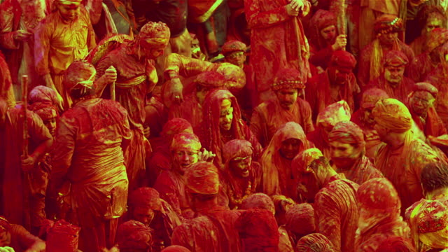 People finishing singing folk songs at Holi, festival of colour, while people throwing colors on them