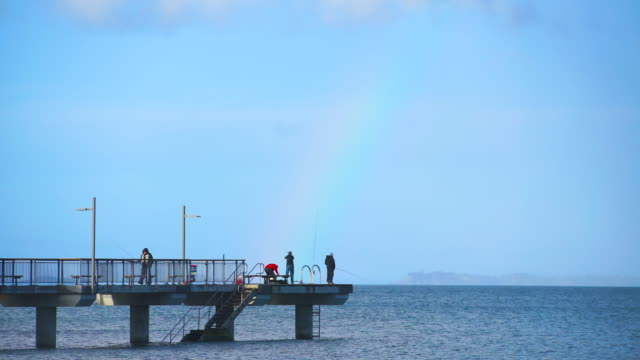 People fishing at Murrays Bay dock with rainbow in background, Auckland, New Zealand.