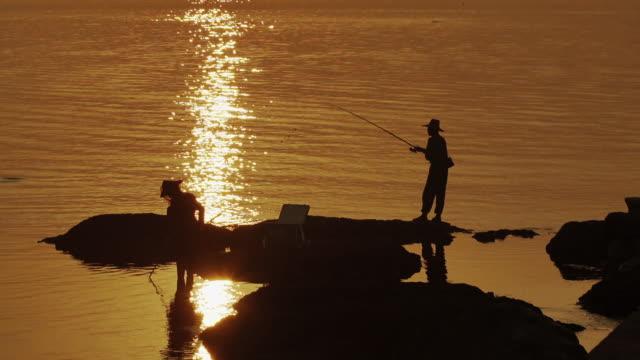People Fishing on Rocks at Sunset