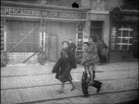 vidéos et rushes de people fleeing with belongings on city street / people running with children during bombings / burning buildings, collapsing. spanish civil war on... - évasion