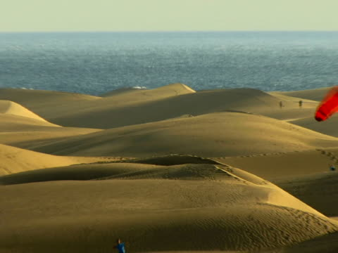 HA WS ZO People flying kite on sand dunes with ocean in background / Maspalomas, Gran Canaria, Spain