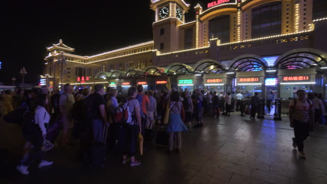 people forming queue while standing at ticket counter in beijing railway station - entertainment building stock videos & royalty-free footage