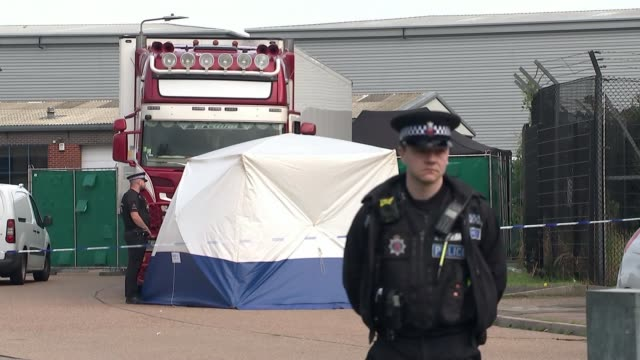 people found dead inside lorry in essex; england: essesx: grays: waterglade industrial park ext police officer standing guard with lorry behind... - エセックス州点の映像素材/bロール