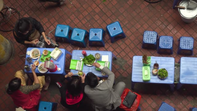 people from vietnam eating directly above view. sitting at plastic little chair and table. dong xuan market at hanoi high angle point of view - traditionally vietnamese stock videos & royalty-free footage