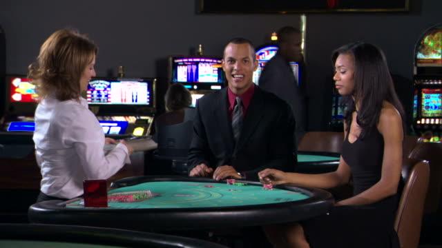 stockvideo's en b-roll-footage met people gambling in casino - man met een groep vrouwen