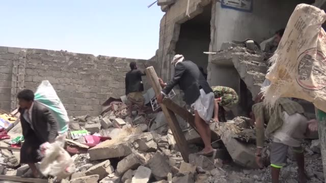 people gather around a heavily damaged building after saudiled coalition's air strikes over arhab district of sanaa yemen on august 23 2017 at least... - yemen stock videos & royalty-free footage
