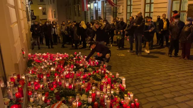 people gather at a makeshift memorial of candles and flowers at the scene of a terror attack where last monday night a gunman rampaged on november... - terrorismus stock-videos und b-roll-filmmaterial