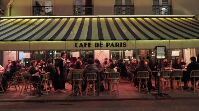 "vídeos de stock e filmes b-roll de people gather at cafe ""cafe de paris"", in the 6th quarter of paris, after french prime minister edouard philippe announced that france will shut... - bar local de entretenimento"