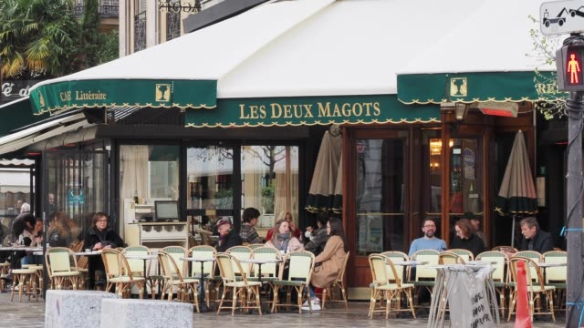 "vídeos de stock e filmes b-roll de people gather at cafe ""les deux magots"", in the 6th quarter of paris. french prime minister edouard philippe announced that france will shut shops,... - bar local de entretenimento"
