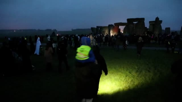 people gather at stonehenge in wiltshire on the winter solstice to witness the sunrise after the longest night of the year. - solstice stock videos & royalty-free footage