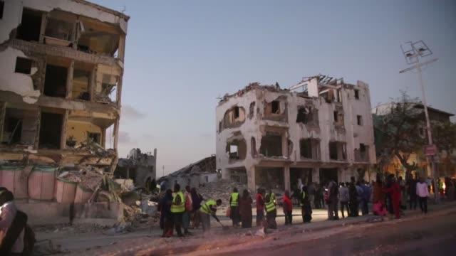 people gather at the site of a car bomb attack near the maka al-mukarama hotel in the somali capital mogadishu on march 01, 2019. al-qaeda-affiliated... - somalia stock videos & royalty-free footage