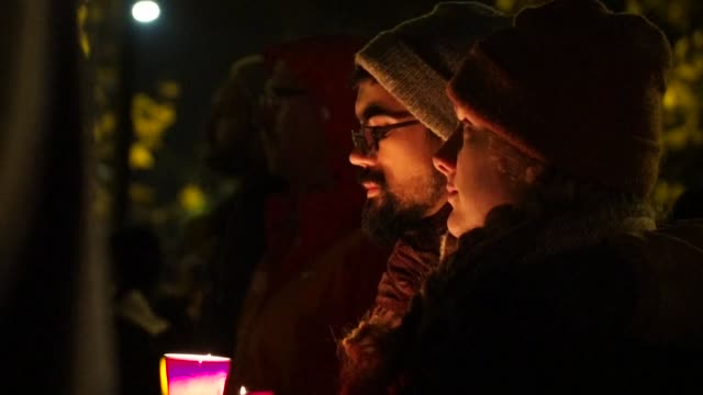 People gather during a vigil honoring those who died in a warehouse fire in Oakland California