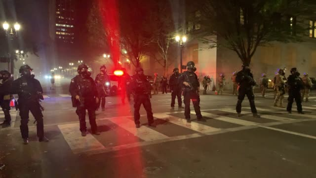 people gather in protest and confrontation with federal police in front of the mark o hatfield federal courthouse in downtown portland as the city... - portland oregon video stock e b–roll