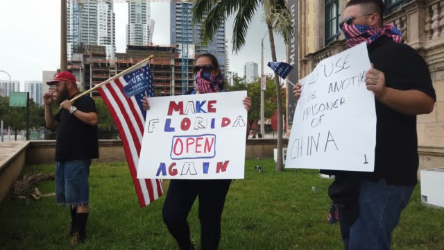 people gather in protest in front of the freedom tower during the coronavirus pandemic on april 25, 2020 in miami, florida. protesters were demanding... - florida us state stock videos & royalty-free footage