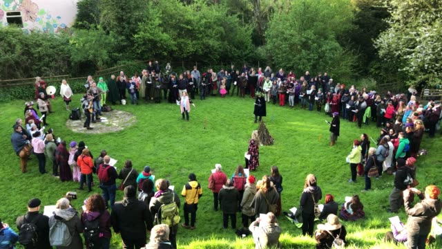 People gather in the Chalice Well Trust Gardens below Glastonbury Tor for a sun rise ceremony as they celebrate Beltane on May 1 2018 in Somerset...