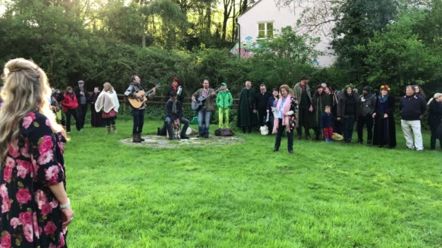 people gather in the chalice well trust gardens below glastonbury tor for a sun rise ceremony as they celebrate beltane on may 1 2018 in somerset... - may day international workers day stock videos & royalty-free footage