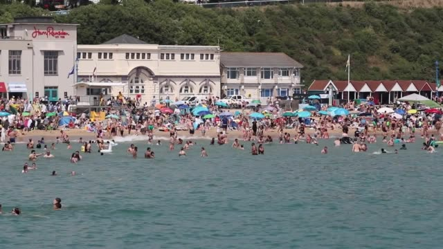 people gather on bournemouth beach as the uk experiences the second hottest day on record. it's possible that the all-time uk record of 38.5c... - 熱波点の映像素材/bロール