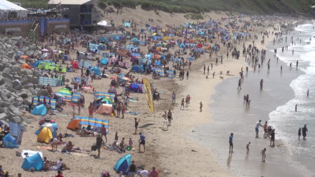 People gather on the beach as surfers compete in a heat of the World Surf League Boardmasters Quicksilver Open at the annual Boardmasters festival at...